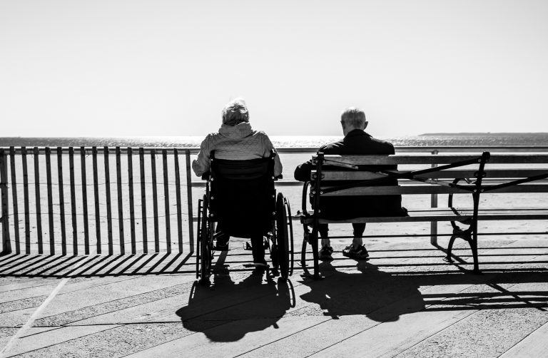 elderly couple sitting together one in wheelchair